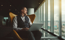 A Handsome Elegant Caucasian Man Entrepreneur Is Sitting In An Orange Armchair With His Laptop And Thoughtfully Looking Outside The Window Of A Luxury Business High-rise On An Urban Landscape