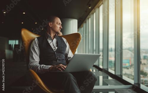 Fotomural A handsome elegant caucasian man entrepreneur is sitting in an orange armchair w