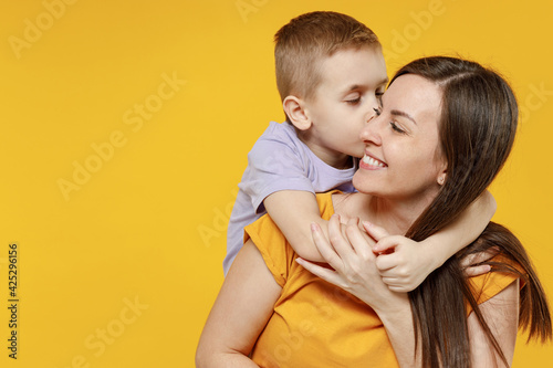 Fototapeta Happy young woman have fun with cute child baby boy 5-6-7 years old in violet t-shirt