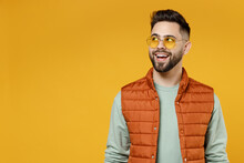 Young Surprised Happy Friendly Cheerful Fun Caucasian Man 20s Years Old Wear Orange Vest Mint Sweatshirt Glasses Looking Aside Isolated On Yellow Background Studio Portrait. People Lifestyle Concept.