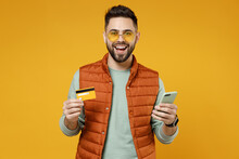 Young Excited Rich Smiling Caucasian Man 20s Wearing Orange Vest Mint Sweatshirt Glasses Using Mobile Cell Phone Credit Bank Card Book Online Look Aside Isolated On Yellow Background Studio Portrait