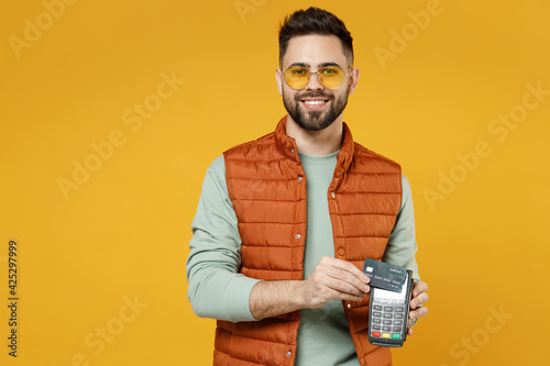 Fototapeta Young rich successful happy man in orange vest mint sweatshirt glasses holding wireless modern bank payment terminal to process and acquire credit card payments isolated on yellow background studio