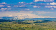 Beautiful Winter Landscape Of Golan Heights: View Of Snow-capped Mount Hermon On A Border With Syria And Lebanon - Israel's Only Ski Resort, With Green Fields And Clouds