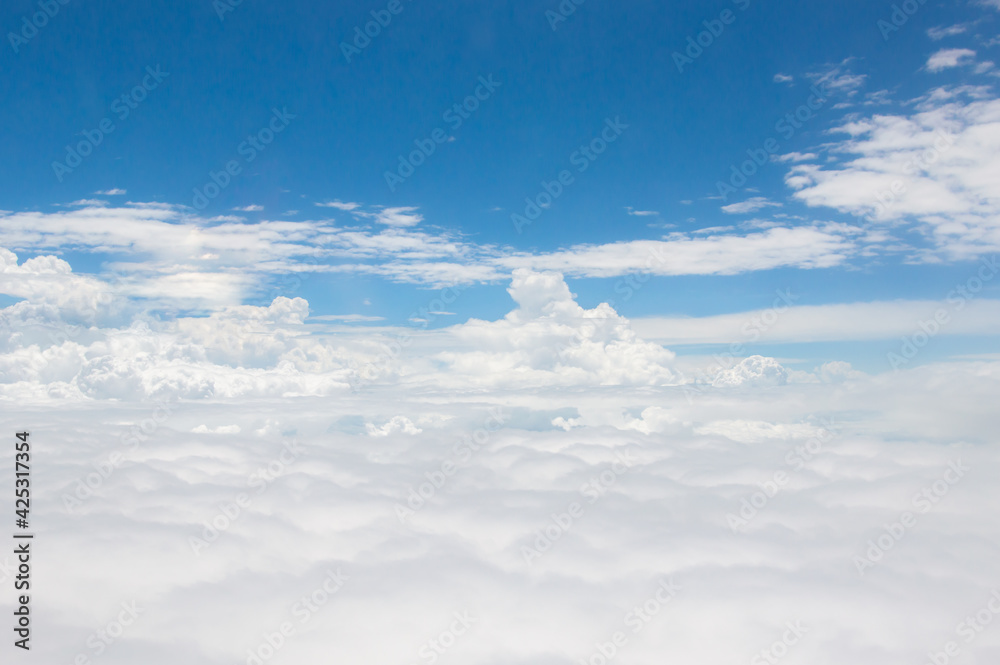 Fototapeta over the clouds,Blue sky with tiny clouds background Beautiful natural view from airplane window above. Background or Wallpaper.blue sky and cloud sky nature.Top view of aircraft