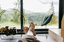 Beautiful Female Feet On Background Of Firewood And Big Window In Modern Chalet, Woman Relaxing