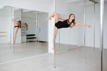 Slim Woman On Pole-dancing Training In Class