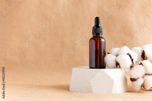 Papel de parede Creative still life with amber glass cosmetic bottles on a concrete podium against a background of kraft paper