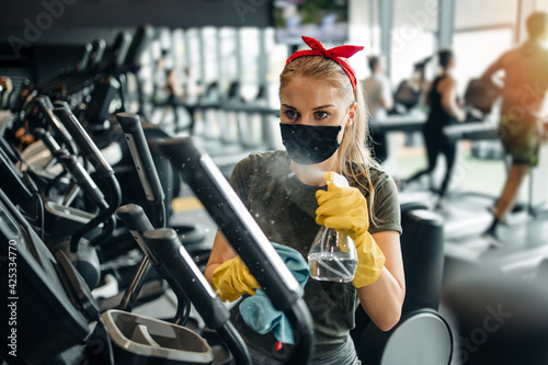 Fototapeta Young female worker disinfecting cleaning and weeping expensive fitness gym equipment with alcohol sprayer and cloth. Coronavirus global world pandemic and health protection safety measures. obraz
