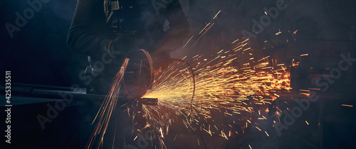 Fotografia Young man grinding metal on steel pipe with flash sparks.