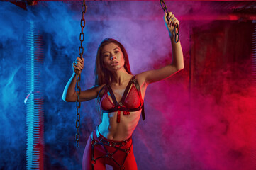 Sexy girl in red bdsm suit holding on to chains