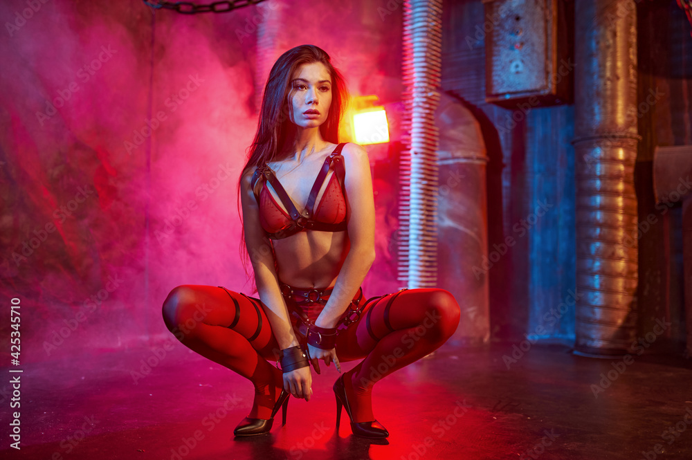 Fototapeta Sexy model in red bdsm suit and handcuffs