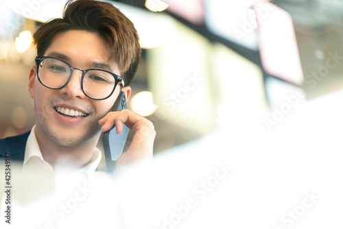 Fototapeta creative agency smart glasses asian male formal cloth conversation with smartphone freelance working with laptop at coworking area office space with freshness with blur office background obraz