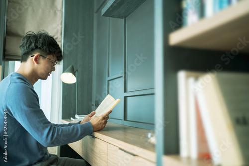 Obraz Male Asian reading a book in bedroom.. - fototapety do salonu