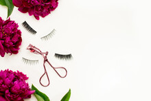 False Eye Lashes, Pink Curler And Flowers Red Peony On White Background. Beauty Concept - Tools For Eyelash Extension.