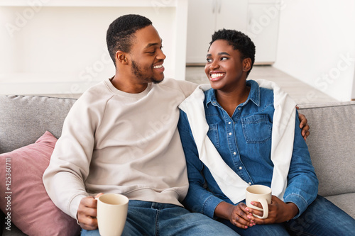 Fototapeta Black couple talking and spending time together sitting on couch obraz