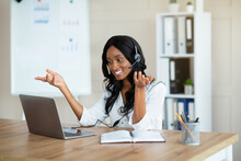 Smiling Entrepreneur Or Office Worker In Headset Speaking With Business Partner, Having Online Videocall In Office