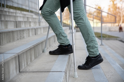 Foto Close up on male legs with crutches on the stairs.