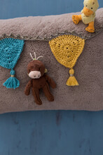 Crochet Garland And Two Funny Dolls Over A Beige Warm Cushion.