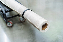 A Roll Of Linoleum Lies On A Transport Cart In The Store's Sales Area. Selective Focus. Cropped Frame