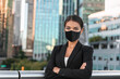 Asian business woman or real estate agent confident portrait wearing face mask for coronavirus prevention in urban city background.
