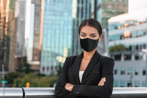Obraz na plátne Asian business woman or real estate agent confident portrait wearing face mask for coronavirus prevention in urban city background