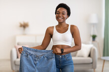 Skinny Black Female Showing Old Large Jeans After Weight-Loss Indoor