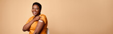 African Female Rolling Up Sleeves Showing Vaccinated Arm, Beige Background