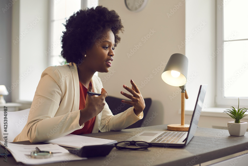 Fototapeta Young african american woman having conference video call using laptop talking to coworker online audience sitting at office desk in evening. Consultation, webinar, tutoring on internet, telecommuting
