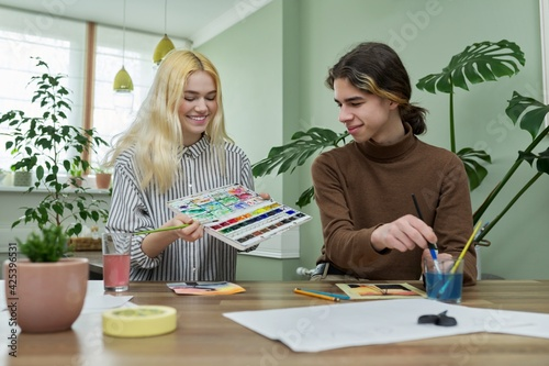 Teenagers guy and girl sitting at table with paints, brushes, drawings Fototapeta