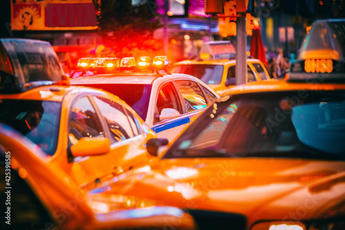 Fotografering New York City Police patrol car flashing beacon siren lights in busy NYC traffic jam with yellow taxi cabs cars