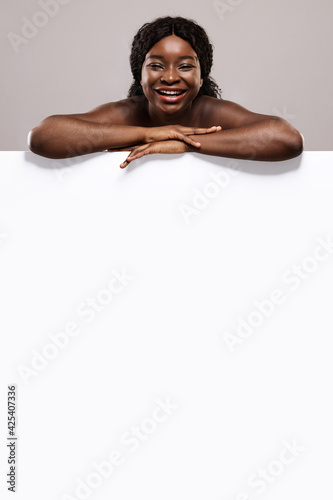 Beauty Offer. Cheerful Naked Black Lady Leaning At White Blank Board