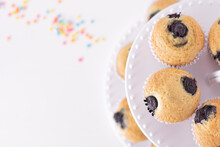 Muffins Presented On A Double-decker Tray, Top View, White Background With Some Colorful Details