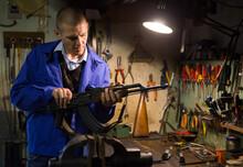 Gunsmith With Kalashnikov Assault Rifle In A Weapons Workshop