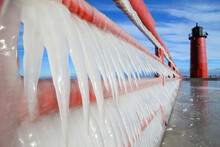 Icicle Covered Red Railings Leading To Red Lighthouse, Milwaukee Pier Head Lighthouse Against Blue Sky