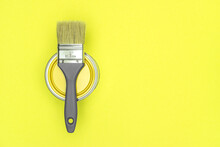 House Renovation Concept. Metal Can Of Yellow Paint With Bristle Brush On Yellow Background
