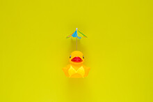 Rubber Duck Wearing Yellow Swimming Suit With Cocktail Umbrella On Yellow Background. Minimal Summer Concept.