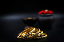 Gold Bangles On A Black Background