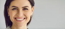 Close Up Of The Face Of A Woman Who Is Sincerely Smiling With A Snow-white Smile On A Gray Background. Millennial Woman With White Teeth. Dental Clinic Advertising Concept. Banner. Place For Text.