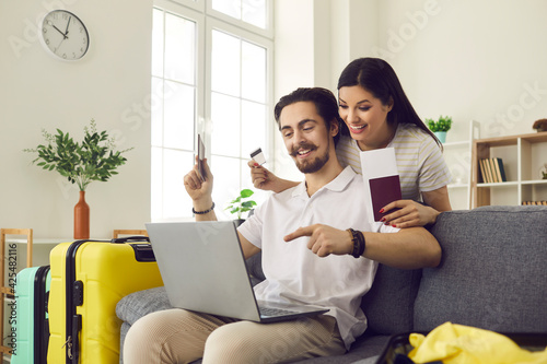 Fototapeta Happy married couple at home using a laptop to pay for tickets and book a hotel room online. Man and a woman with already collected suitcases are ready for vacation. Concept of summer vacation abroad. obraz