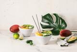 Bowls of fresh salad with mango, shrimps and vegetables on light background
