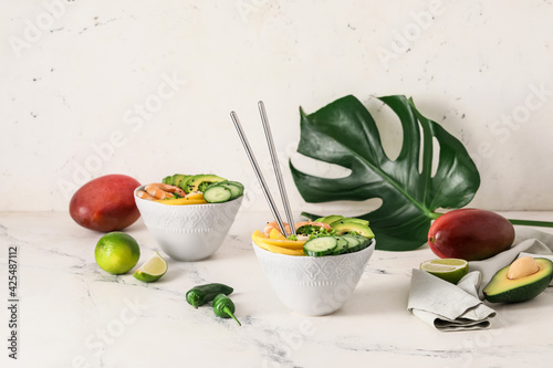 Bowls of fresh salad with mango, shrimps and vegetables on light background