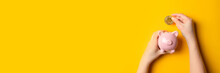 Businessman Putting Bitcoin Into Piggy Bank On Yellow Background With Copy Space. Panoramic Banner Background