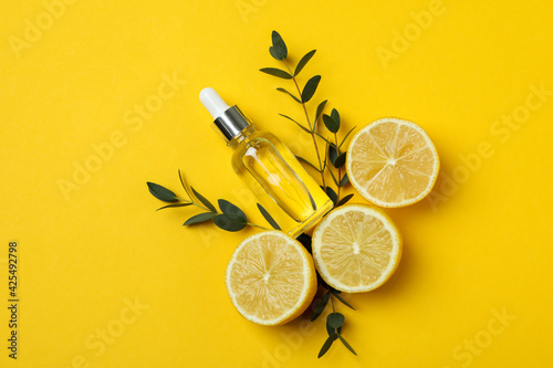 Concept of natural cosmetics with lemon oil on yellow background