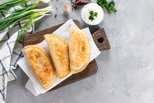 Uzbek eastern Tatar cuisine, cheburek with meat and greens on a wooden board. Cheburek - fried pie with meat and onions. Traditional dish of Turkish and mongolian. Top view. Copy space.