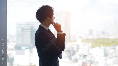 Photo 窓から街を見て考えるビジネスマン