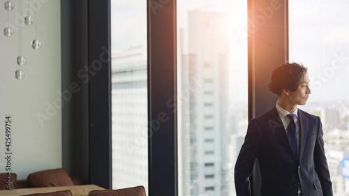 Canvas Print 窓から街を見て考えるビジネスマン