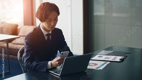 Fototapeta パソコンとスマホを見ながら深刻な表情のビジネスマン obraz
