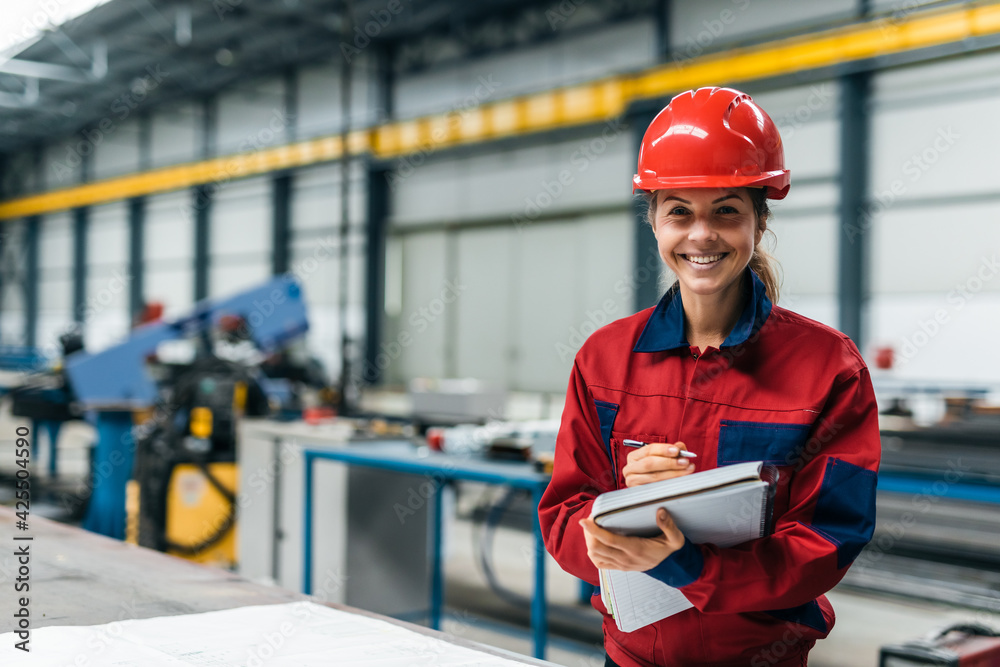 Fototapeta Portrait of a smiling engineer in protective work wear in industrial building.
