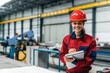 canvas print picture - Portrait of a smiling engineer in protective work wear in industrial building.