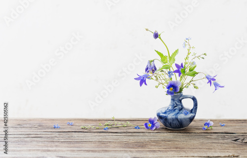 Canvas Print summer flowers in blue jug on old wooden table